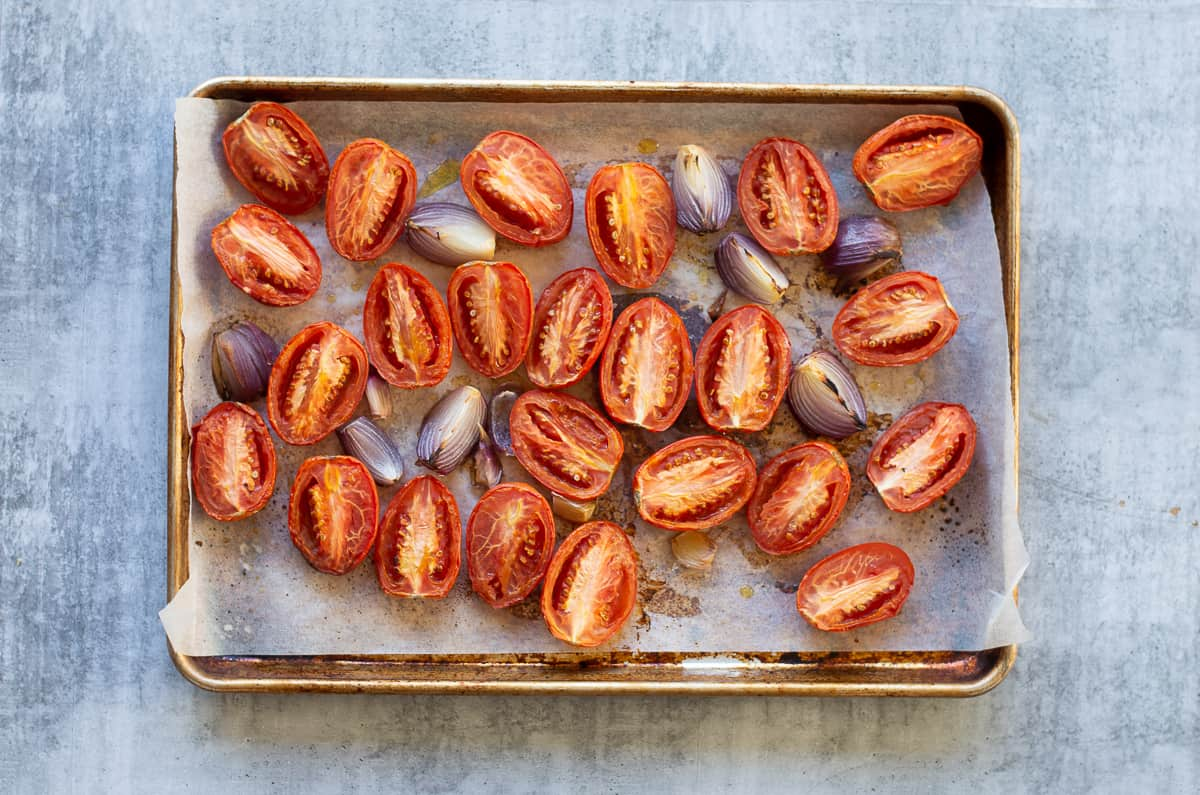 Roasted tomatoes, red oinion and garlic cut up on baking tray