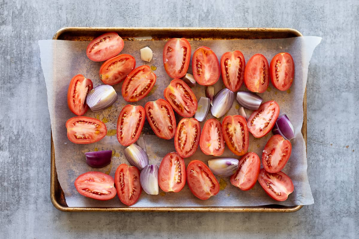 Halved tomatoes, onion and garlic on a baking tray ready to be roasted.
