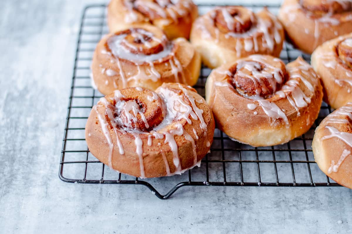 Cinnamon rolls drizzled with icing on a baking rack.