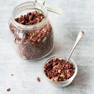 Homemade Chocolate Granola in a glass bowl and jar with silver spoon