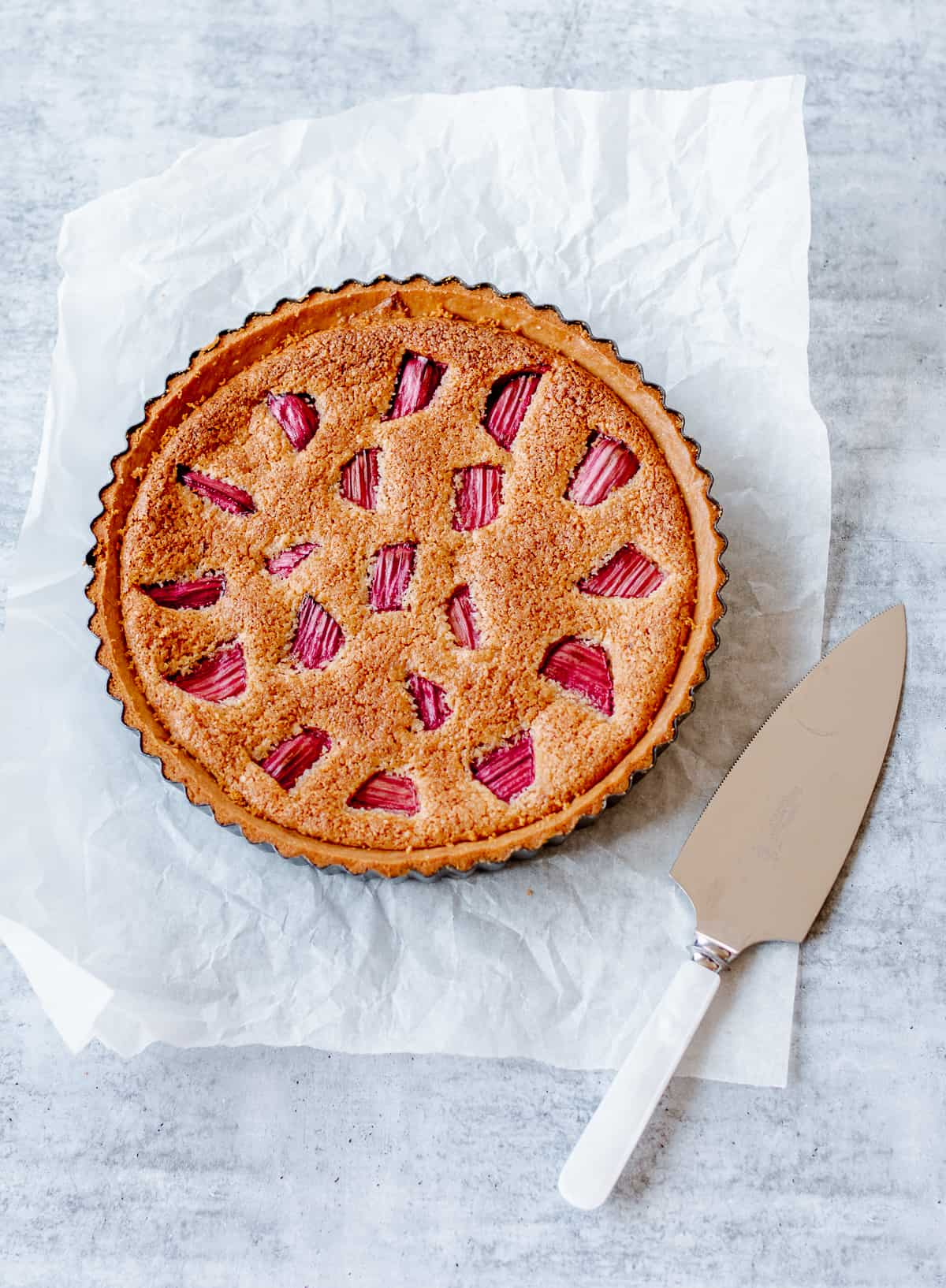 Baked Rhubarb Frangipani tart in round tin with serving spatula