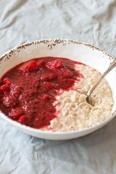 Apple and Rasberry Compote with porridge in a white bowl