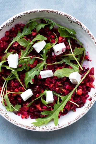 Beetroot, feta and rocket salad in white bowl with fork