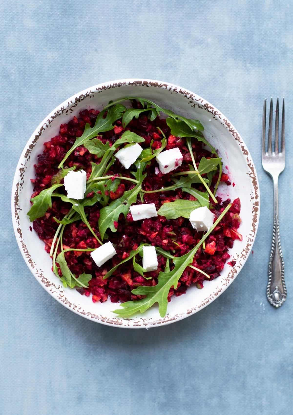 Beetroot, rocket and feta salad in a white bowl with a fork