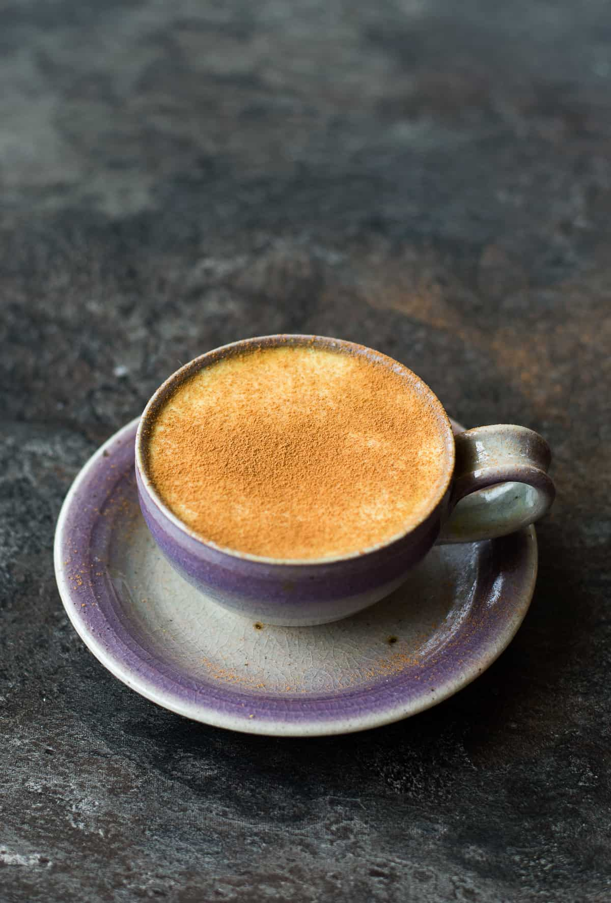 Turmeric Coffee Latte in a purple/light blue cup and saucer on dark backgroud