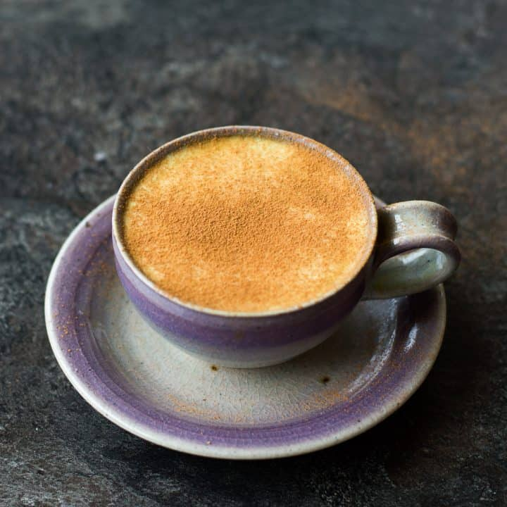 Turmeric Coffee Latte spinkled with cinnamon in a purple/blue cup and saucer on dark background