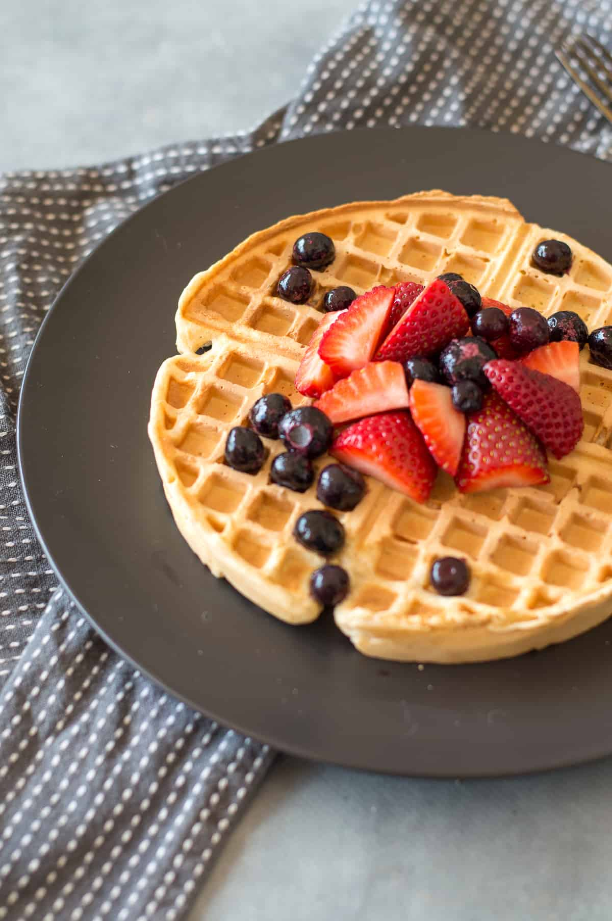 Wholemeal Waffles topped with strawberries and blueberries on dark grey plate
