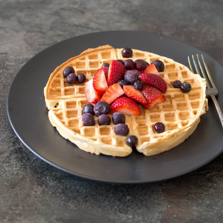 Wholemeal waffles topped with strawberries and blueberries on dark plate