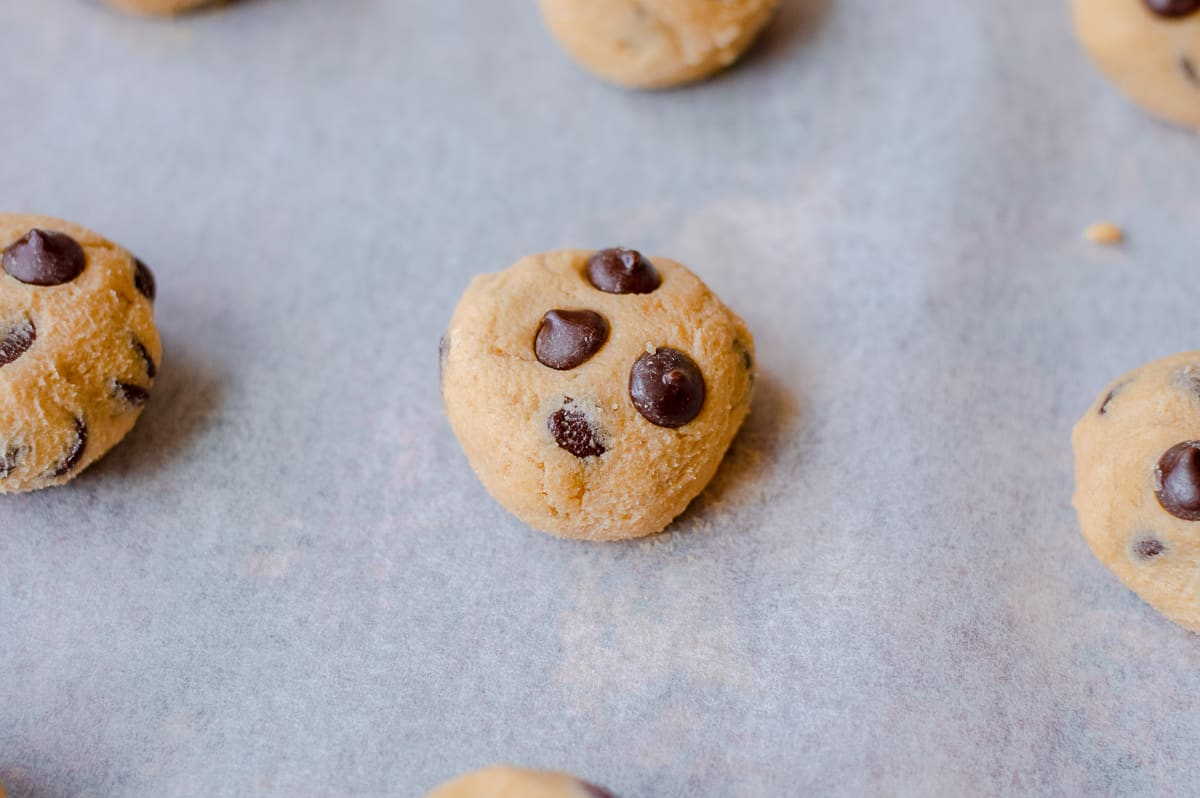 Raw chocolate chip cookie dough ball on baking sheet