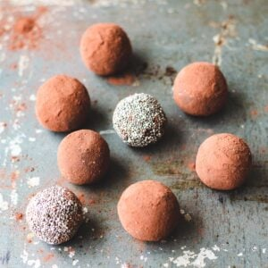 Chocolate chia bliss balls sitting on a baking sheet.