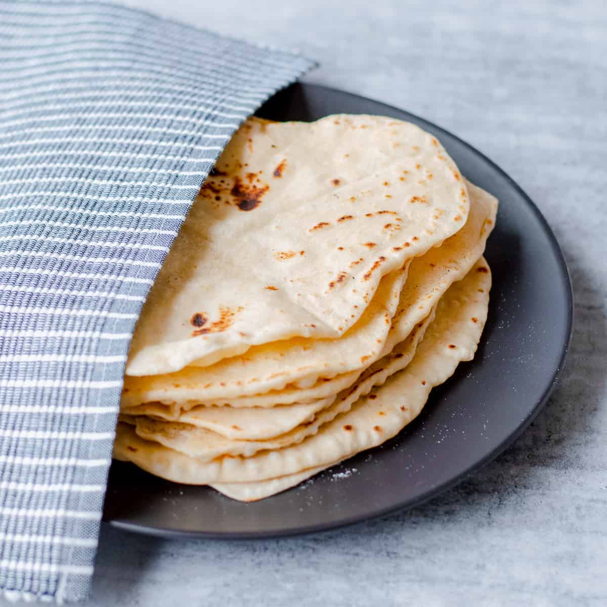 Homemade flour tortillas on black plate half covered with blue and white striped tea towel.