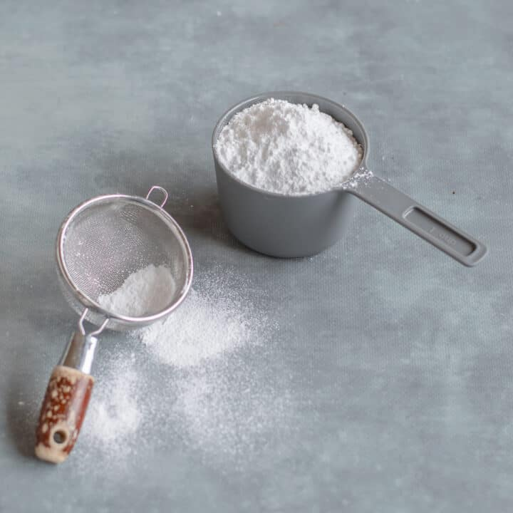 Icing sugar in a grey cup with sifter