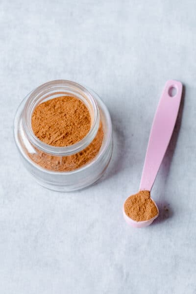 chai spice mix in glass jar with pink spoon