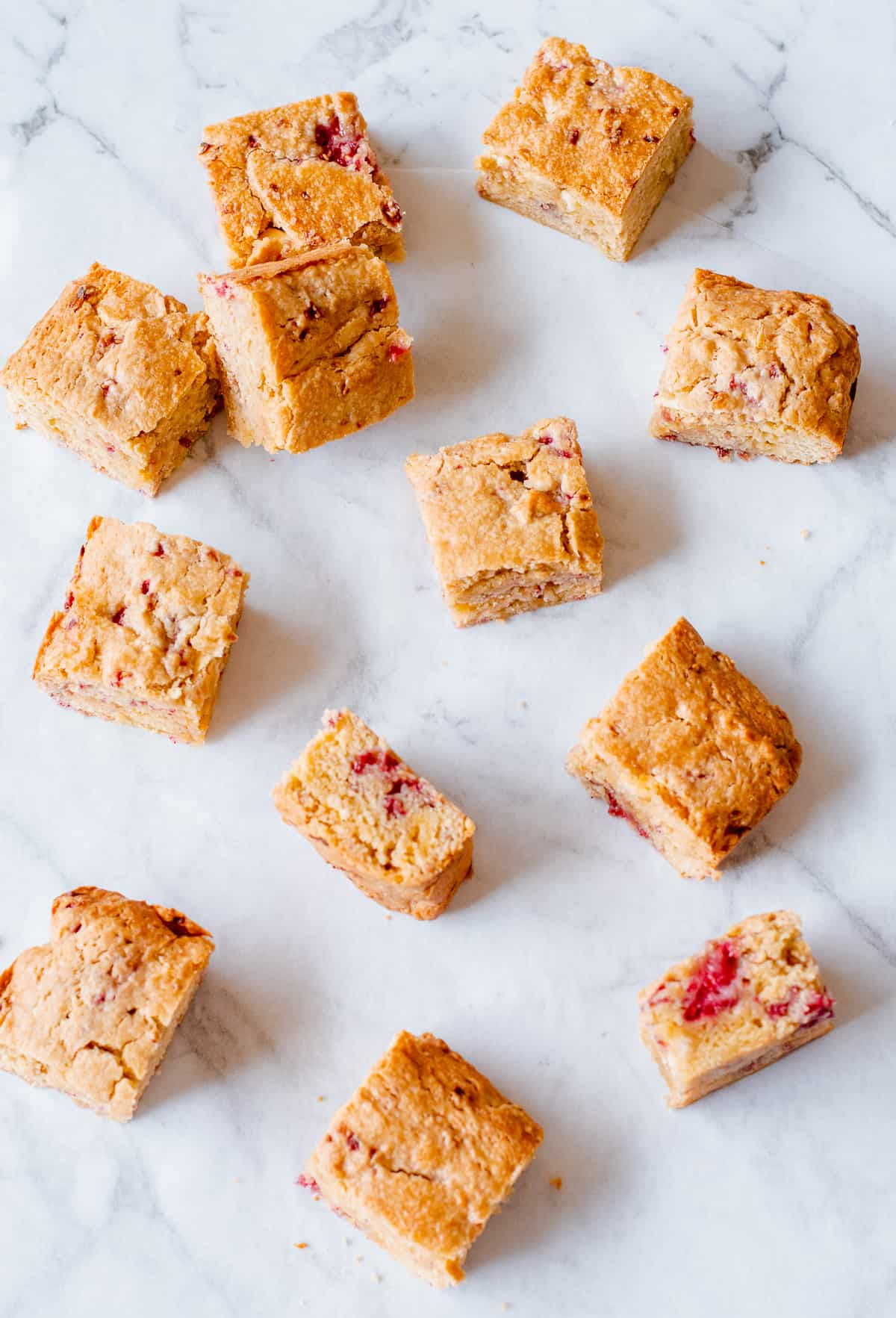 white chocolate and rasberry blondies on a white background