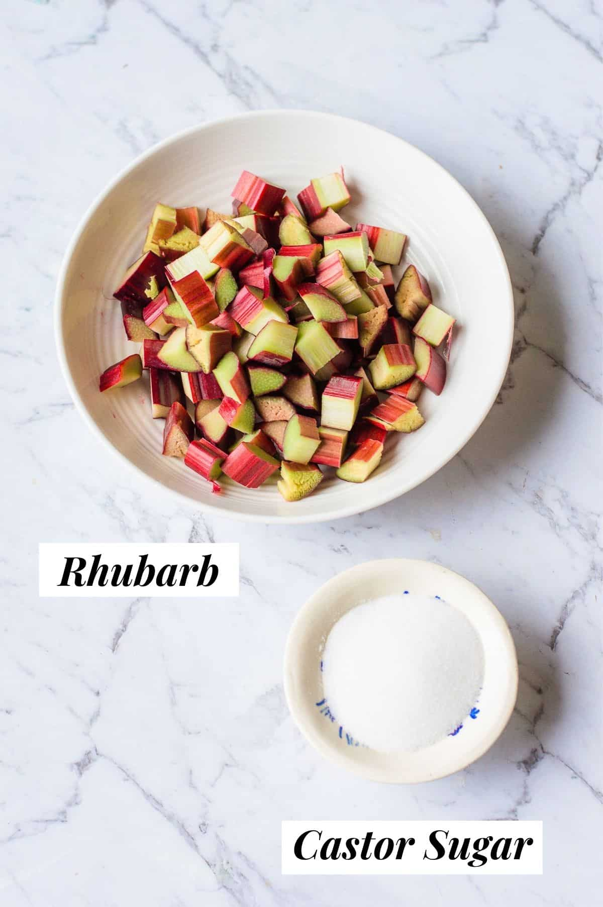 Rhubarb and castor sugar on a marble background.