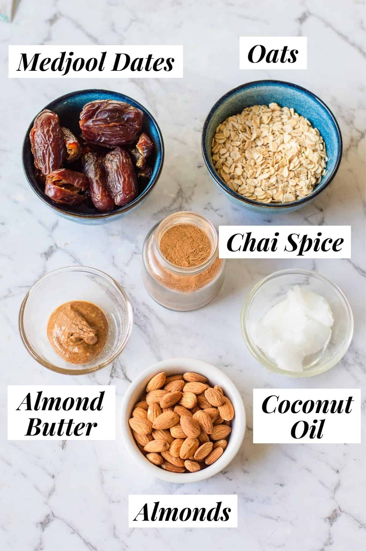 Medjool dates, almond butter, oats, chai spice, almonds and coconut oil on a marble background.