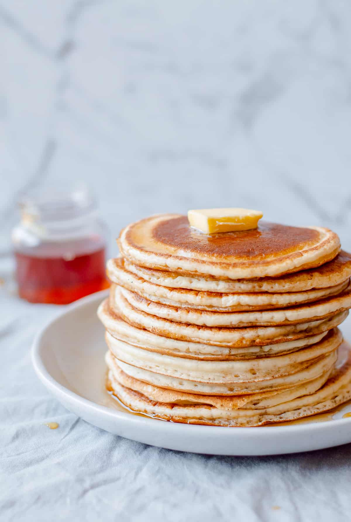 A stack of pancakes with butter on top and maple syrup.