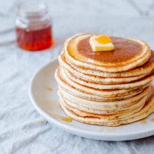 Pancake stack with butter and maple syrup.