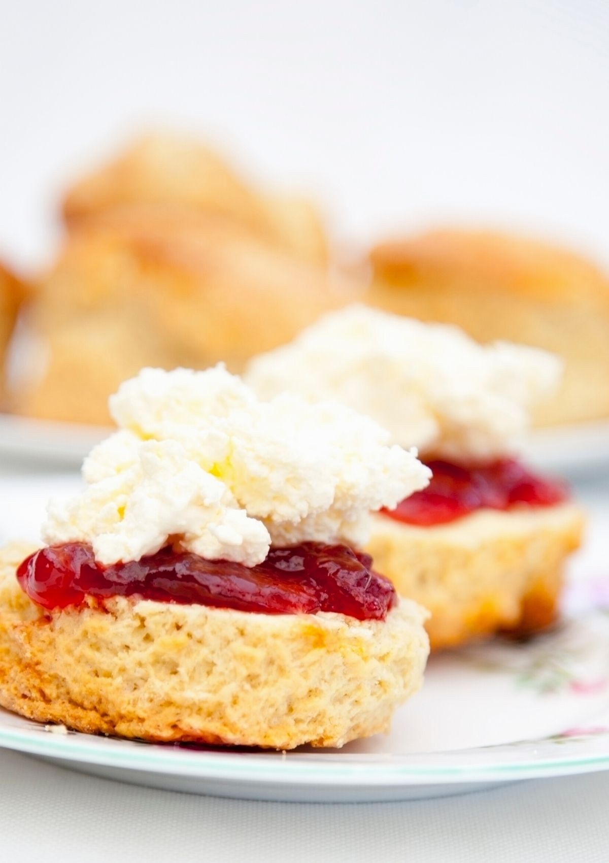 A close up image of scones with strawberry jam and cream.