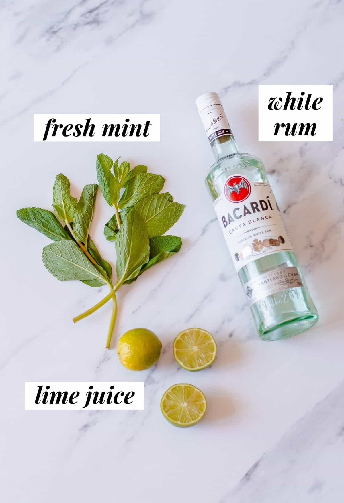 fresh mint, limes and bacardi rum sitting on a white marble background.