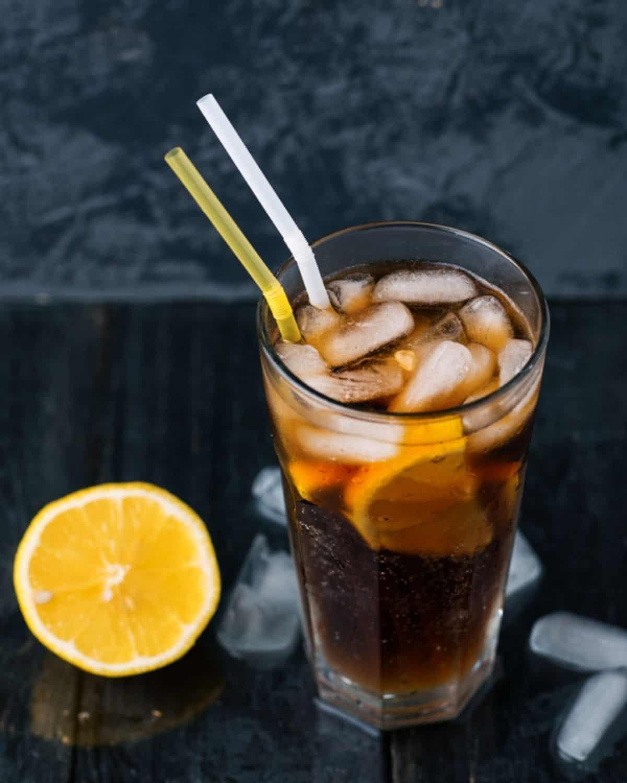 Long island iced tea cocktail in tall glass with lemon.