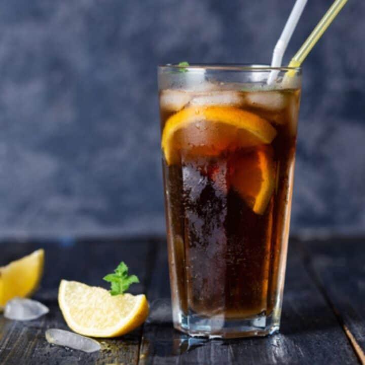 Long Island Iced Tea in a tall glass with lemon wedge.