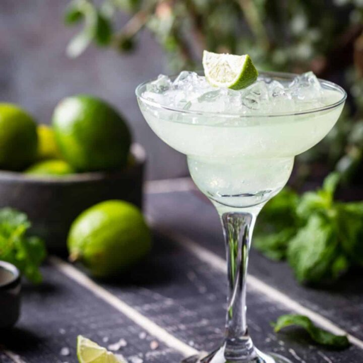 Lime Margarita in a glass with a bowl of limes in the background.