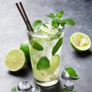 A Mojito in a tall clear glass with ice, mint leaves and limes.